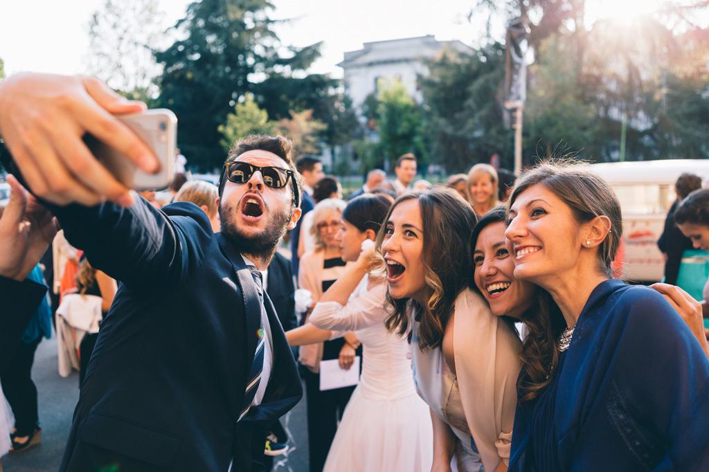 Gli ospiti si scattano selfie dirimpetto alla chiesa dopo il matrimonio