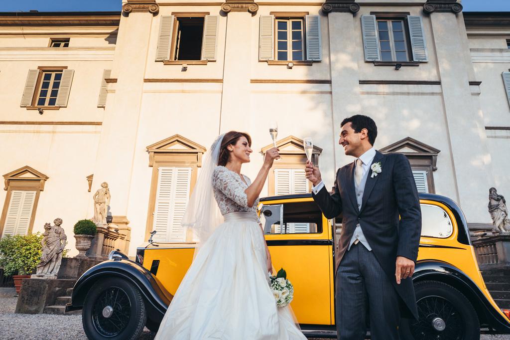 Gli sposi appena usciti dalla macchina brindano a una lunga vita insieme