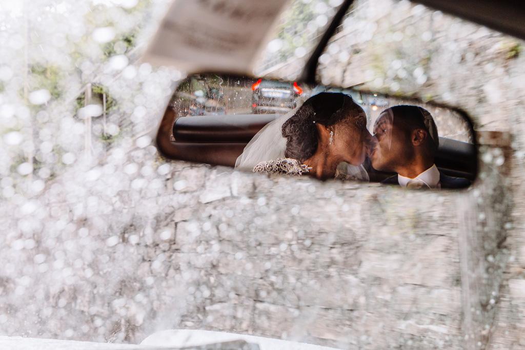 I due sposi si baciano riflessi sullo specchietto della Rolls Royce
