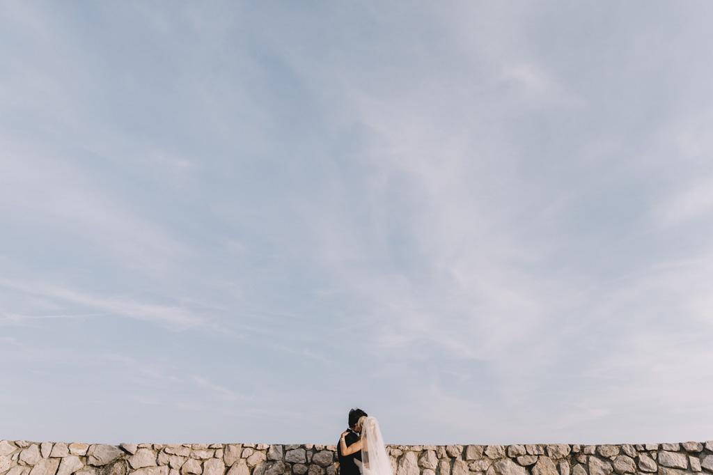 I due sposi si baciano sotto un cielo celeste in uno scatto di Alessandro Della Savia