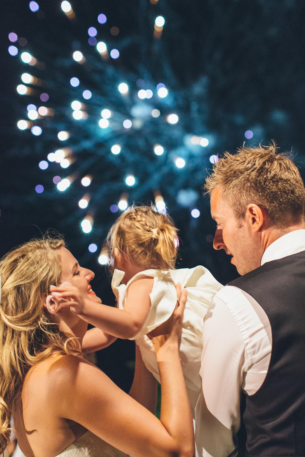 Gli sposi stringono una bambina durante i botti d'artificio in uno scatto di Della Savia