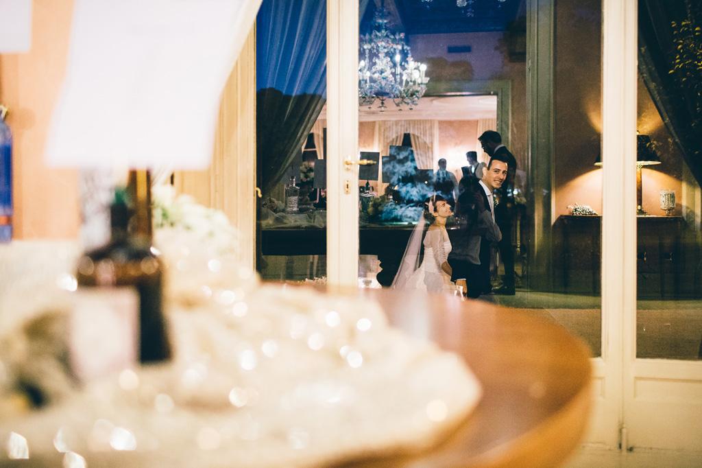 I due sposi passeggiano riflessi tra i vetri di Villa Mattioli