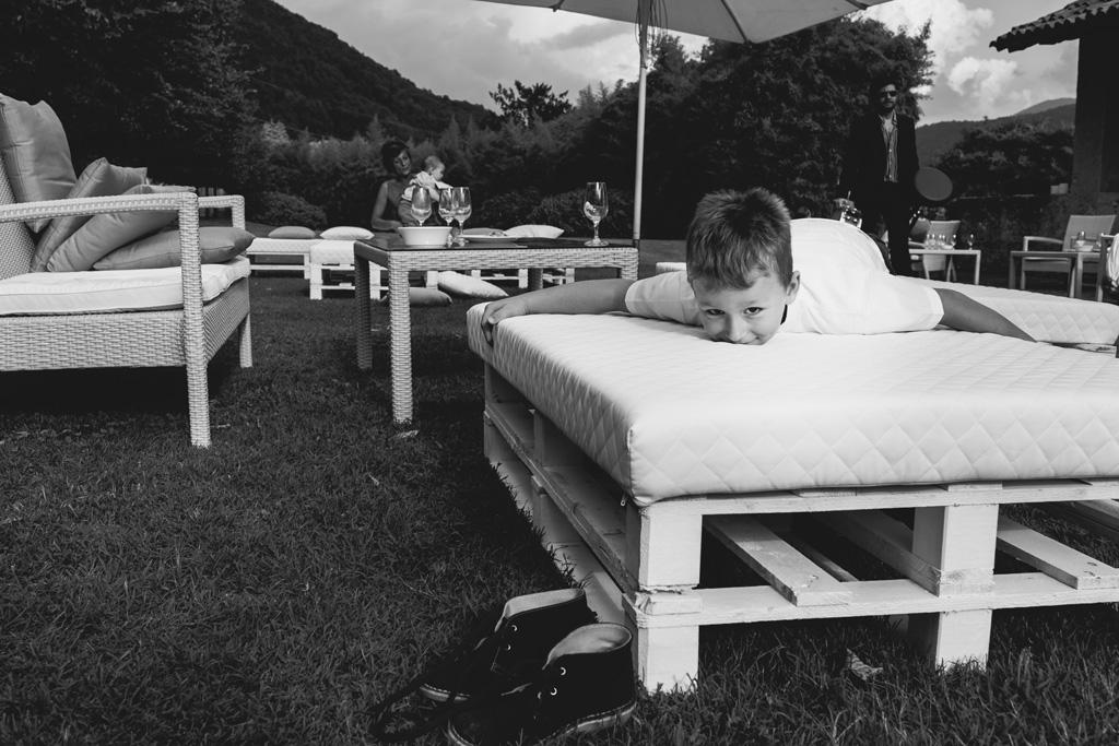 Un bambino sorride sdraiato su un divano nel cortile di Villa Della Porta Bozzolo