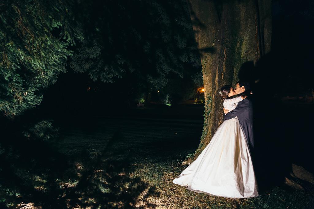 Lo sposo bacia la sposa nello scenario bucolico di Villa Caroli