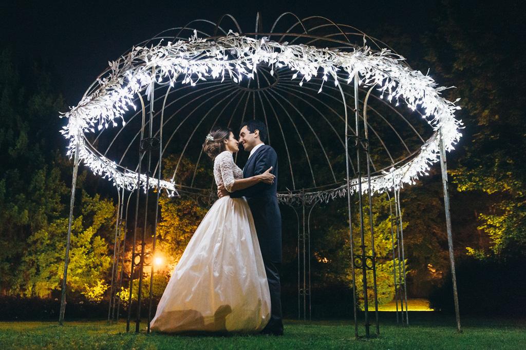 Gli sposi, Riccardo e Beatrice, si guardano intensamente sotto il gazebo adornato e illuminato di Villa Caroli