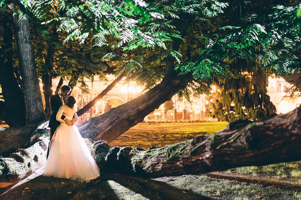 Gli sposi si baciano di fianco a un albero imponente e sullo sfondo brillano le luci di Villa Mattioli