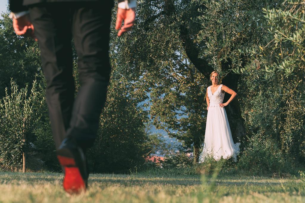 La sposa sorride allo sposo prima di posare nuovamente per il fotografo