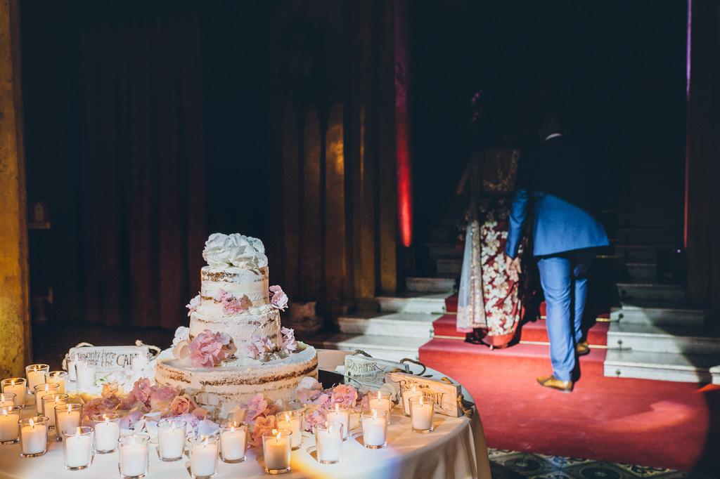 Gli sposi superano la torta dalla penombra della sala