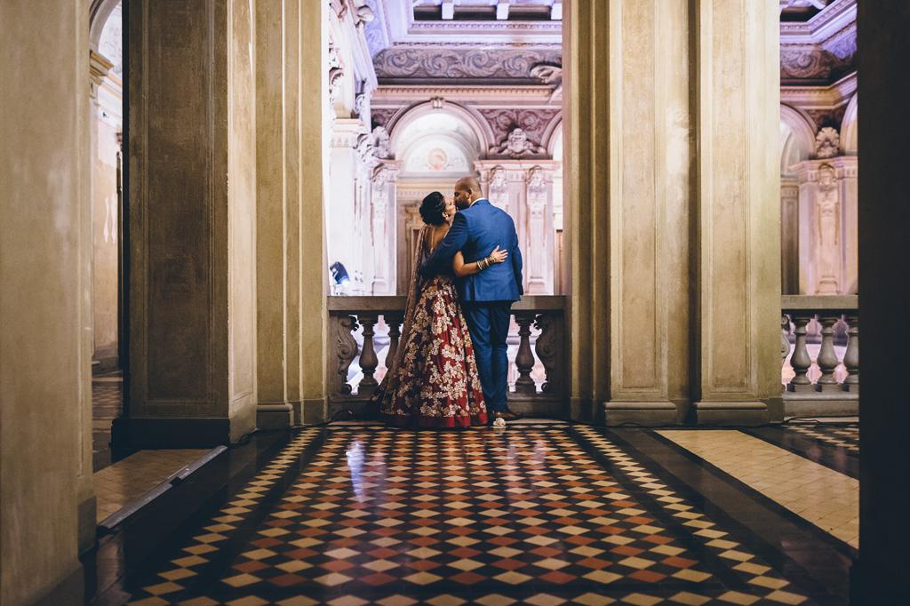I due sposi si baciano dal balcone interno di Villa Erba