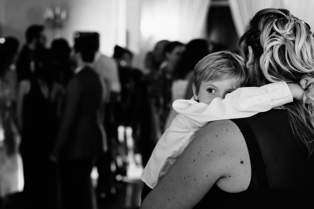 Un bambino si aggrappa alla madre durante la festa dopo il matrimonio