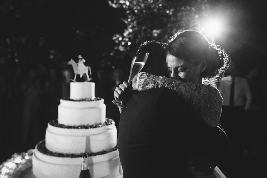 La sposa abbraccia lo sposo dopo il primo taglio della torta nunziale