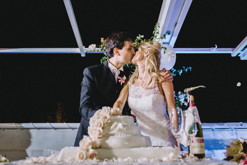 I due sposi tagliano la torta nunziale mentre si baciano