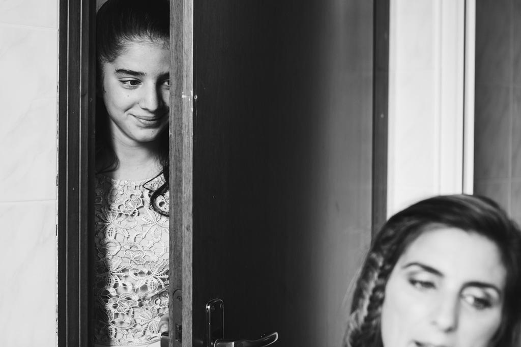 Una bambina sbircia la sposa dalla fessura della porta
