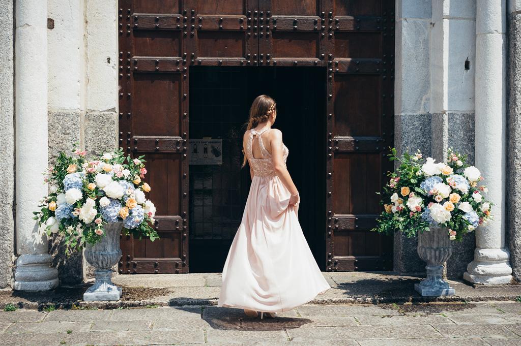 Una damigella si sofferma davanti all'entrata della chiesa