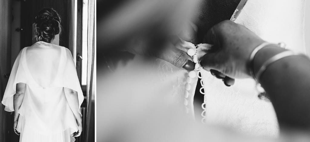 Una damigella abbottona il vestito della sposa