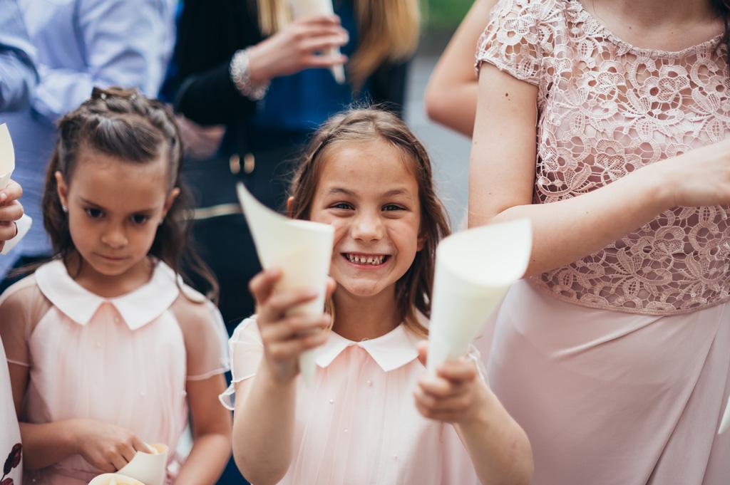Una bambina conserva un cono di rose da lanciare agli sposi