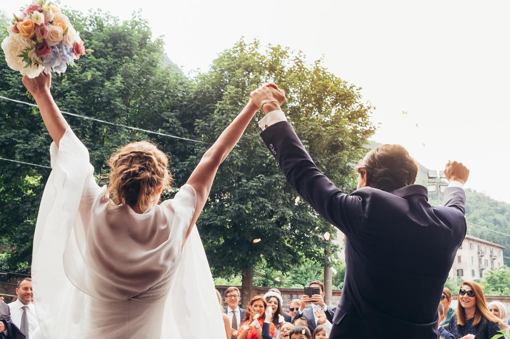Gli sposi alzano le braccia al cielo finalmente congiunti in matrimonio