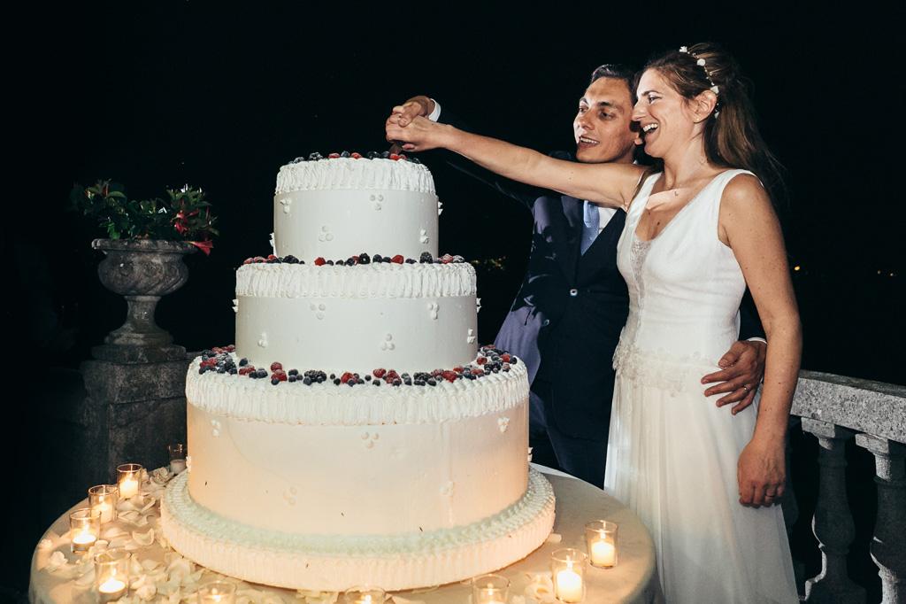 I due sposi tagliano la torta nunziale fotografati da Alessandro Della Savia