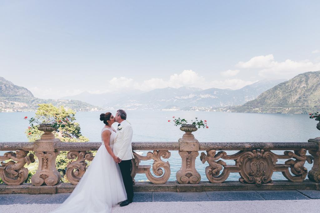 I due sposi si baciano davanti allo sfondo mozzafiato del Lago di Como fotografai da Alessandro Della Savia