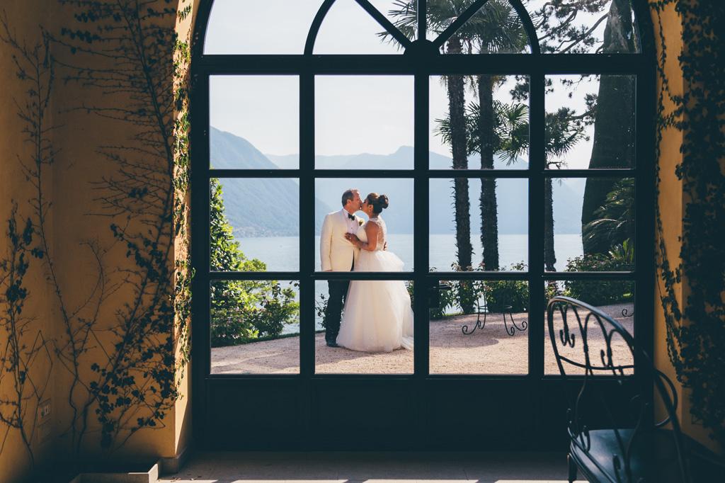 Gli sposi si baciano dirimpetto alle vetrate di Villa Serbelloni