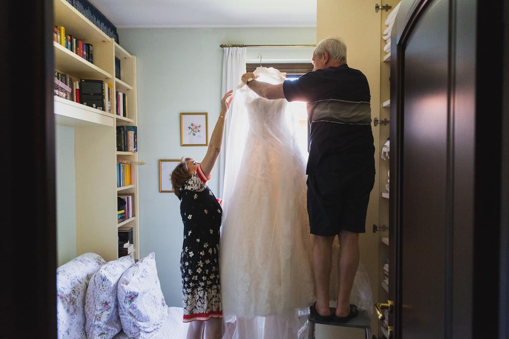 La madre e il padre della sposa prendono il vestito della sposa