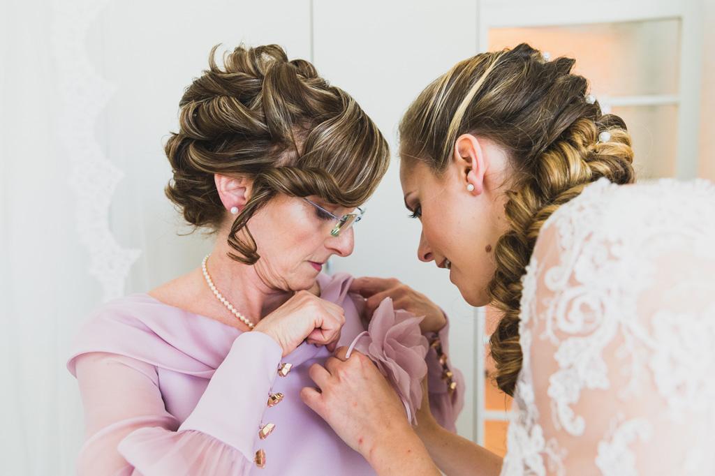 La sposa Sarah sistema il vestito della madre