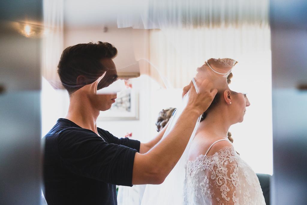 Il parrucchiere acconcia i capelli della sposa