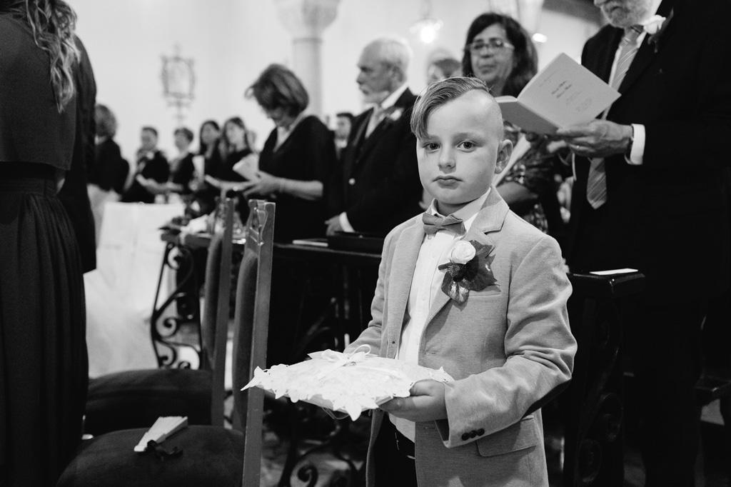 Un bambino custodisce le fedi nunziali sopra un candido cuscinetto