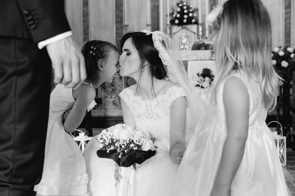 La sposa bacia amorevolmente una bambina in uno scatto rubato da Alessandro Della Savia