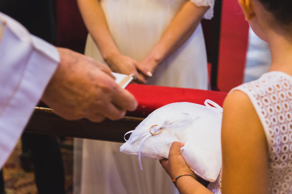 Una bambina consegna le fedi nunziali sopra un candido cuscinetto