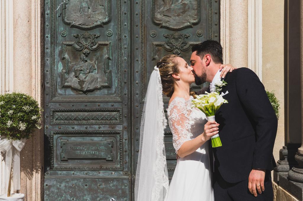 Andrea bacia la sposa Sarah dirimpetto alla chiesa dopo la cerimonia di matrimonio