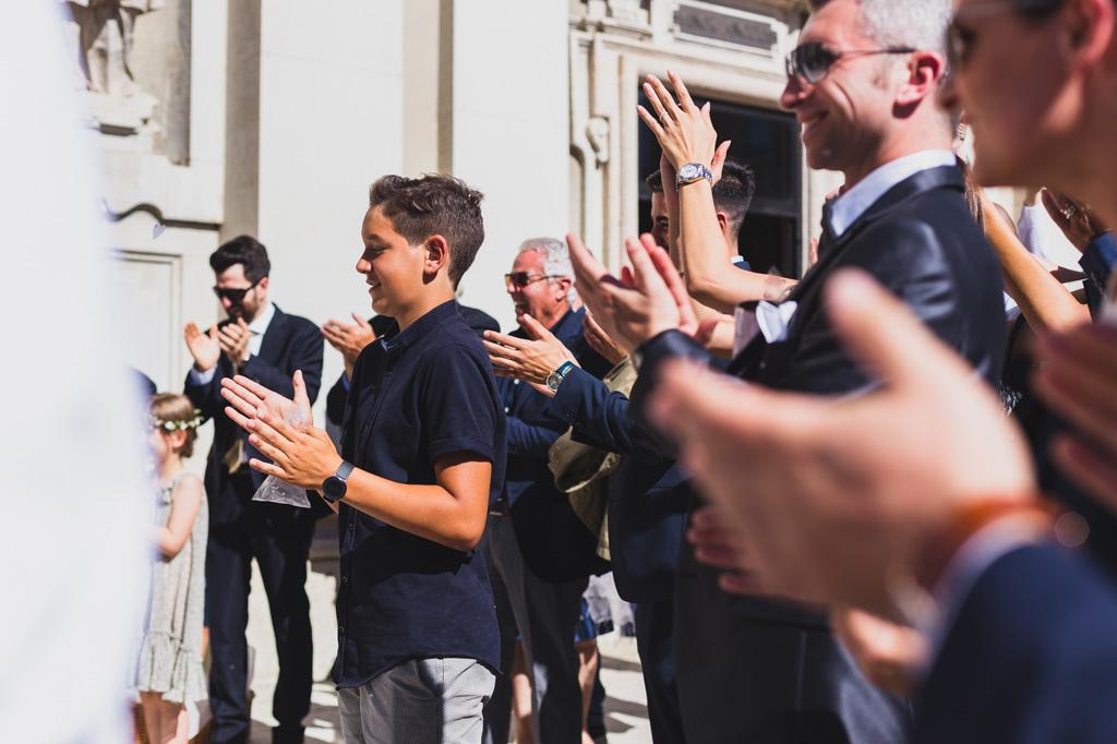 Gli applausi scroscianti degli invitati all'arrivo degli sposi