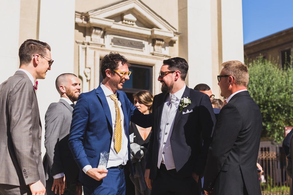 Lo sposo scambia parole e sorrisi con amici davanti alla chiesa
