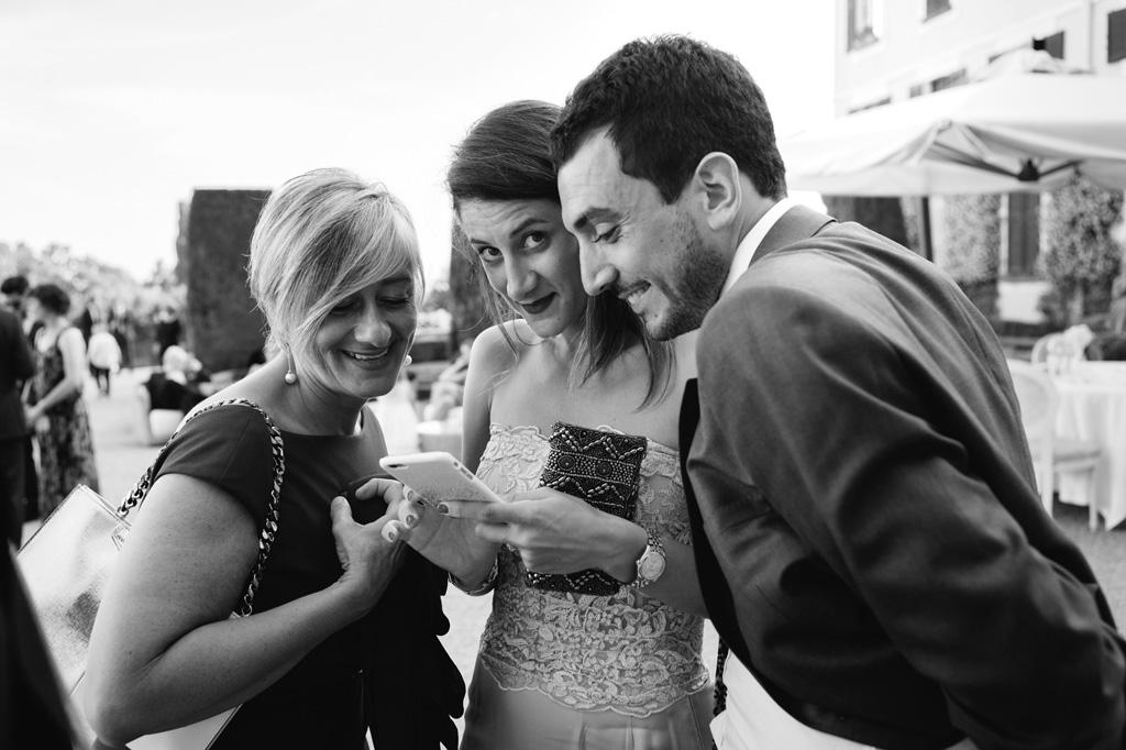 Gli ospiti si divertono a guardare le fotografie con gli sposi