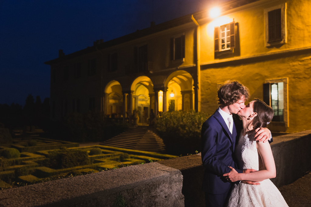 I due sposi, Davide e Eleonora, si baciano durante il crepuscolo ripresi dal fotografo Alessandro Della Savia
