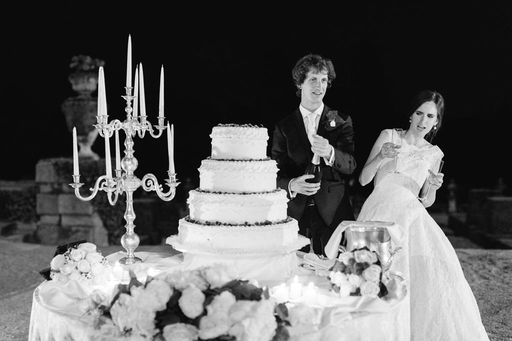 Gli sposi festeggiano con uno champagne e la torta nunziale