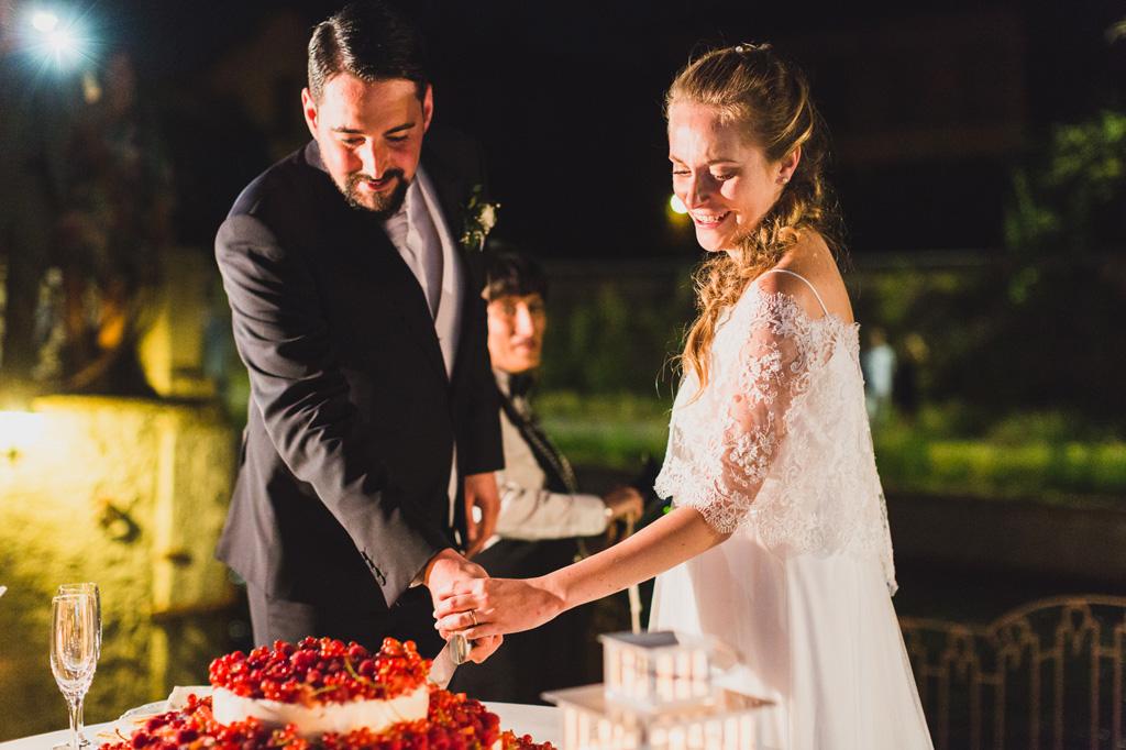 Gli sposi, Andrea e Sarah, tagliano la prima fetta della torta nunziale in uno scatto di Alessandro Della Savia