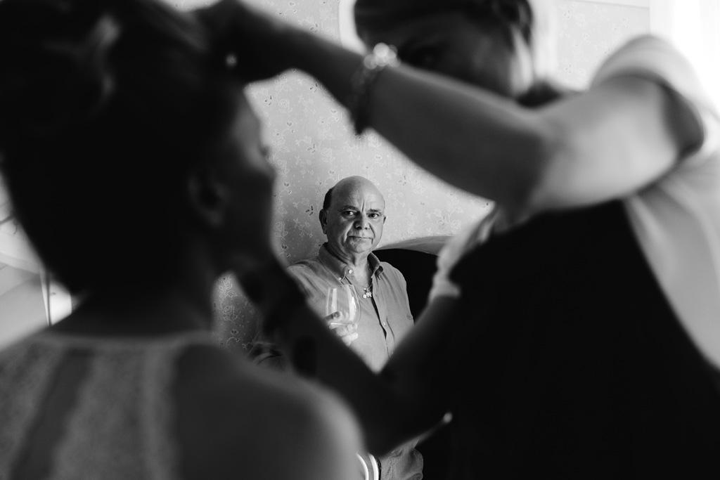 Il padre osserva la sposa mentre viene truccata
