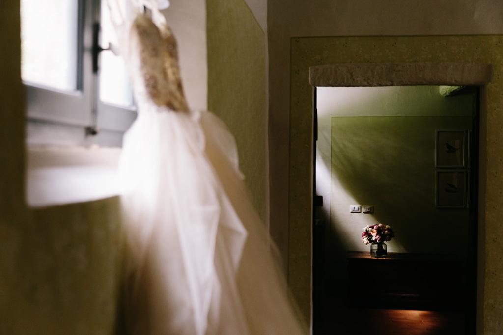 Il vestito della sposa appeso alla finestra prende una luce meravigliosa