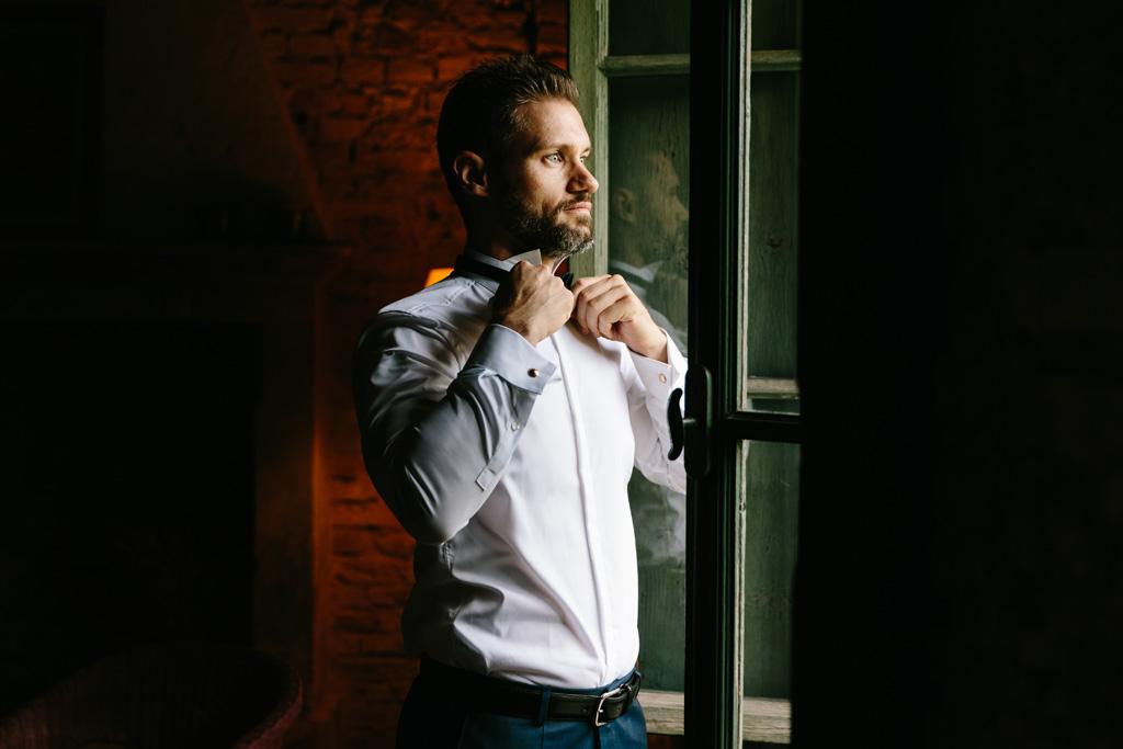 Lo sposo si sistema la camicia davanti alla finestra della sua camera