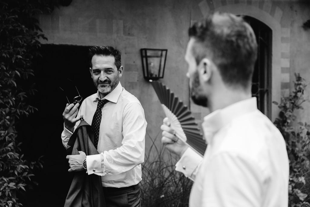 Lo sposo si fa aria con un ventaglio mentre parla con un amico
