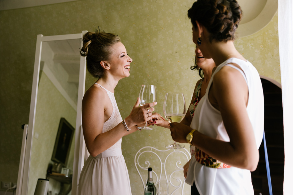 La sposa parla con le amiche nella sua camera prima di terminare il trucco