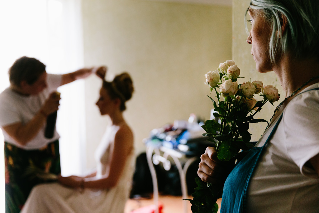 Ultimi ritocchi all'acconciatura della sposa mentre la truccatrice osserva con le rose in mano