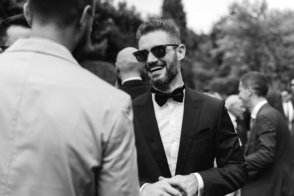 Lo sposo con gli occhiali da sole parla con gli invitati