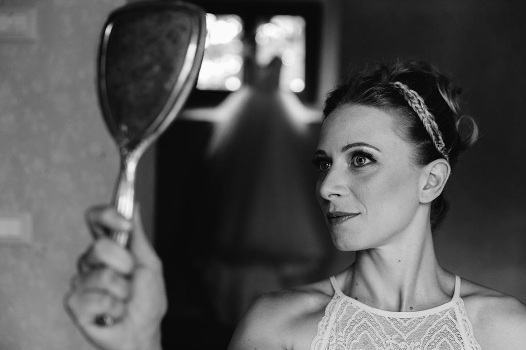 Laura si guarda allo specchio per vedere il risultato finale del trucco
