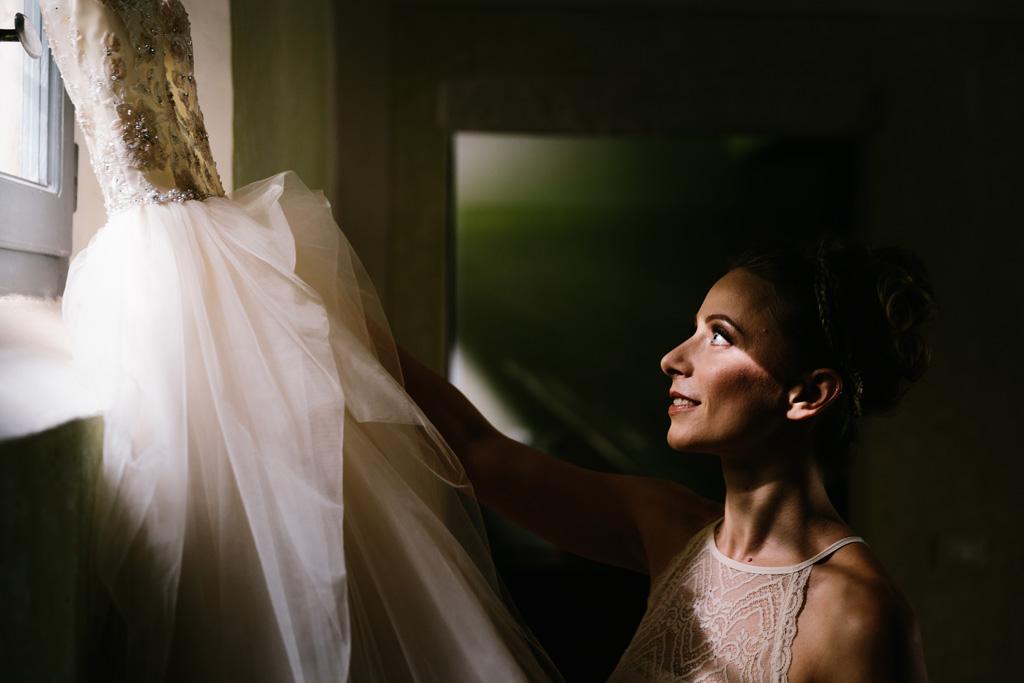 La sposa prende il suo abito bianco appeso alla finestra illuminata da una luce splendida