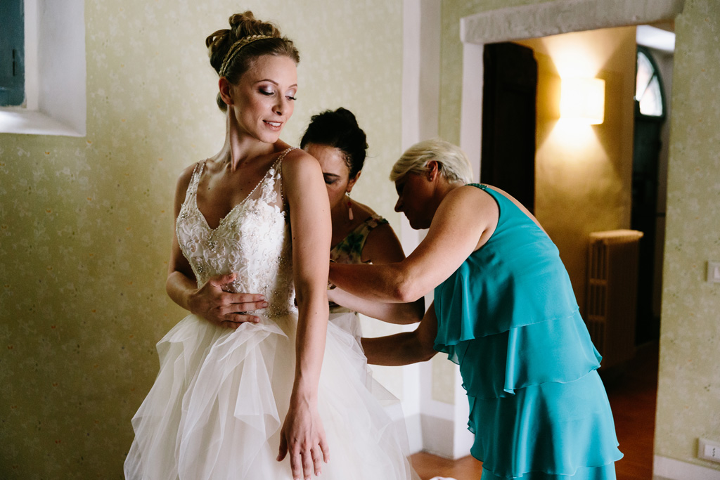 La mamma e l'amica allacciano l'abito alla sposa
