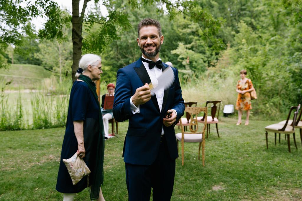 Lo sposo si fa aria con un ventaglio bianco mentre aspetta la sposa