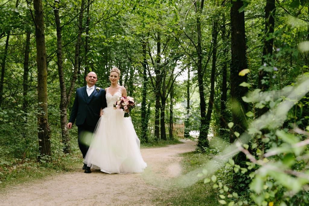 La sposa e il padre attraversano il parco che porta alla cerimonia