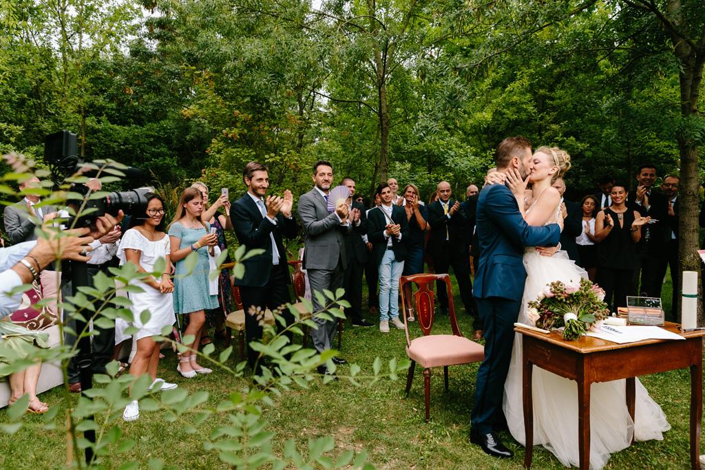 Gli sposi si baciano al termine della cerimonia mentre gli invitati applaudono
